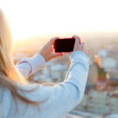 Frau fotografiert Stadt mit Handy