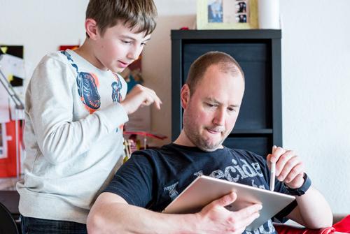 Vater Lukas erklärt Janis etwas an einem Tablet.