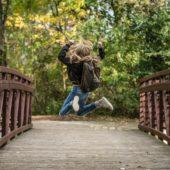 Une petite fille saute de joie sur un pont