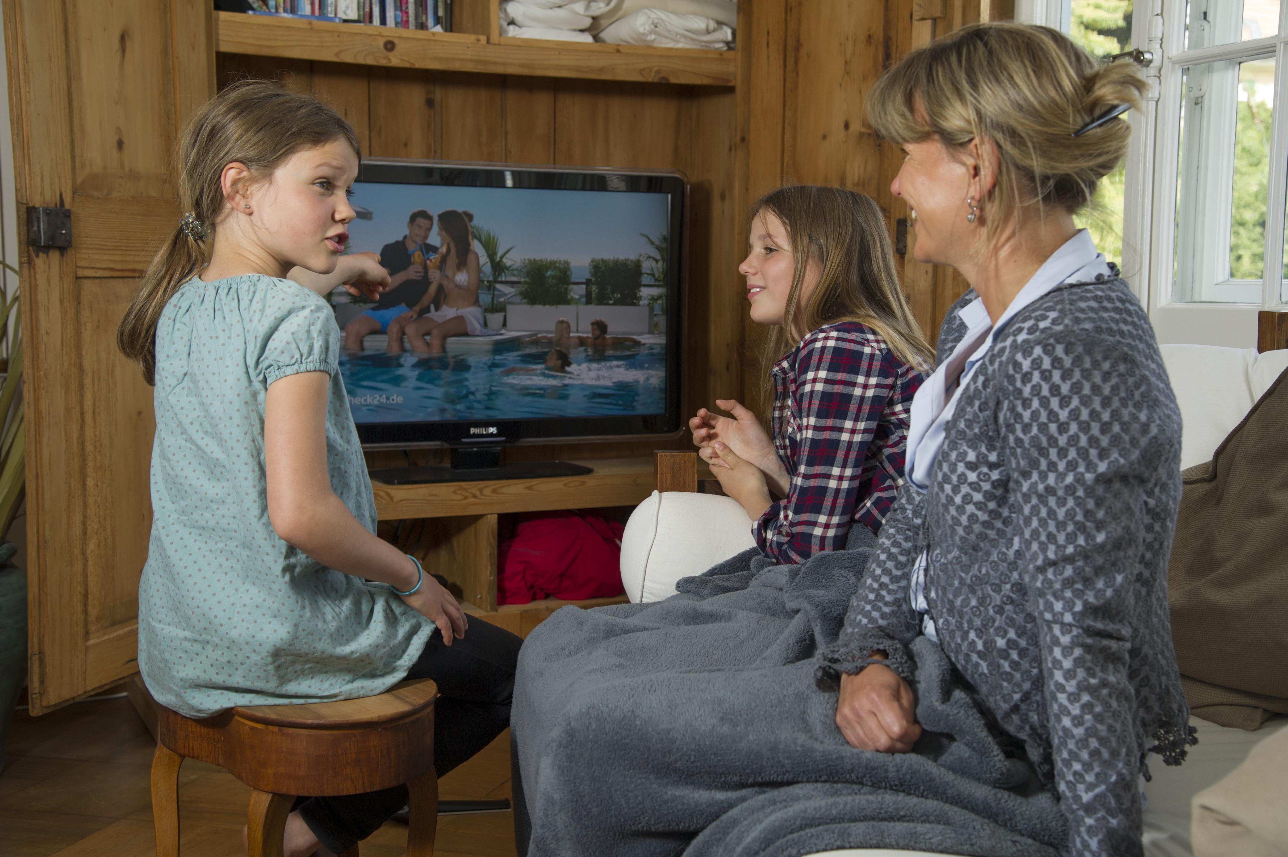 Mutter und Töchter diskutieren über die Sendung, die heute im Fernsehn geschaut werden darf.