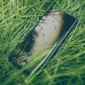 Ein Handy liegt im feuchten Gras.