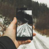 Mann fotografiert Winterwanderweg mit seinem Smartphone.
