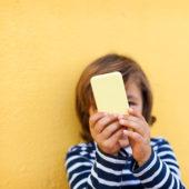 Garçon avec un téléphone portable devant son visage.