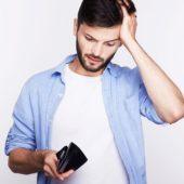 Mann schaut verzweifelt in leere Brieftasche