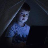 Kind im Dunkeln mit Bildschirm