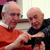 Peter Ritter (à gauche) regarde quelque chose sur le téléphone portable que lui montre un autre participant au cours.