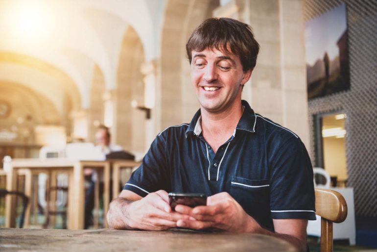 Un Marcel Roesch souriant avec un téléphone portable équipé d'un clavier help2type.