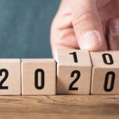 Hand dreht Kombination von Zahlenwürfeln von 2010 auf 2020