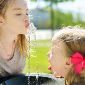 Zwei Mädchen trinken an einem Brunnen.