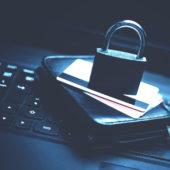 Portemonnaie, Kreditkarte und Schloss liegen auf einer Tastatur