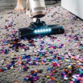 Staubsauger saugt Glitzerpalletten vom Teppich