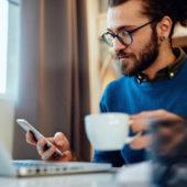 Mann arbeitet zuhause am Laptop und hat eine Kaffeetasse in der Hand.