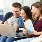 Drei junge Menschen die vor dem Laptop sitzen und sich sichtlich freuen.