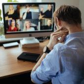 Mann sitzt vor dem Bildschirm und sieht müde aus.